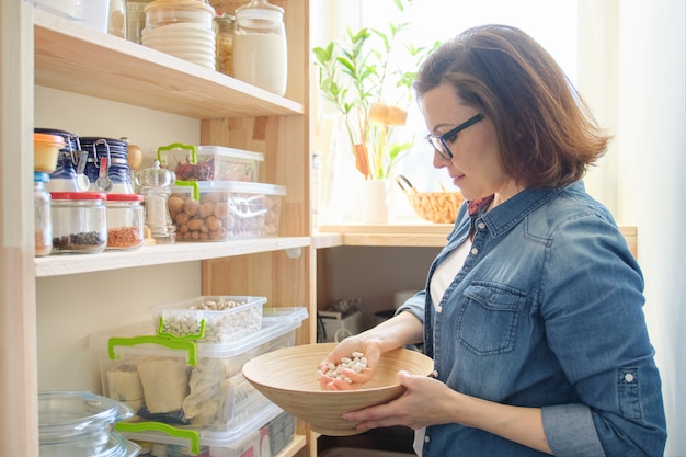 Woman in pantry with bowl of white beans. storage cabinet in kitchen