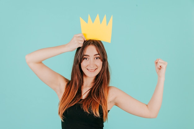 Woman in paper crown showing muscle