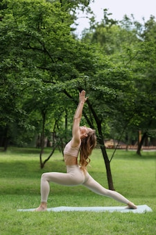 Woman in the park in summer practices yoga in the morning
