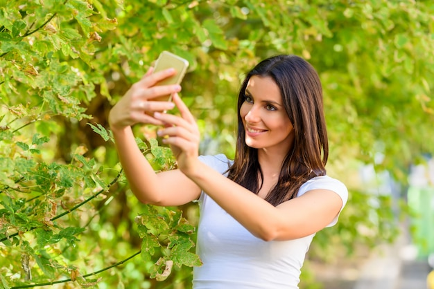 A woman in a park taking a selfie with her smartphone