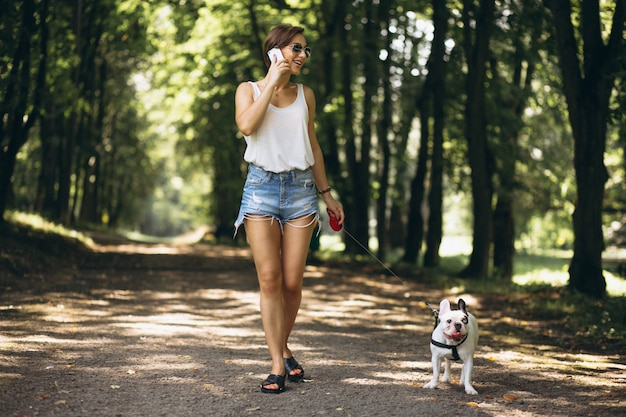 Woman in park with french bulldog talking on the phone
