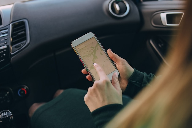 Woman passenger in a car with a map on a smartphone prepares a route