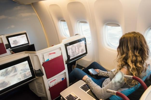 飛行機のビジネスクラスの女性の乗客