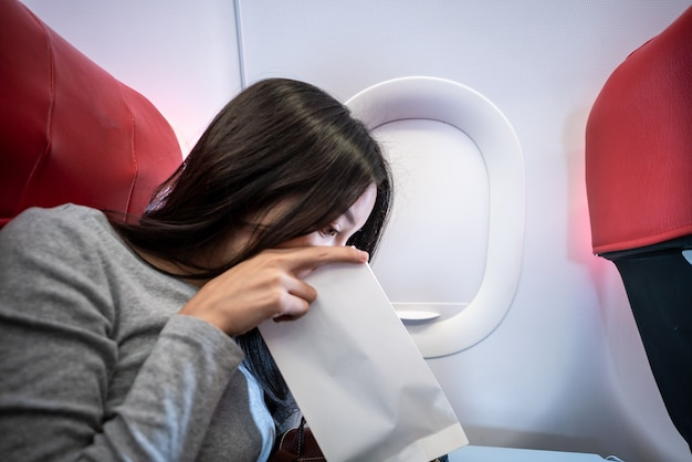 Woman passenger on the plane vomited in a paper bag