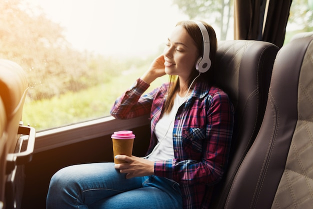 Woman on the passenger seat of the bus listens to music