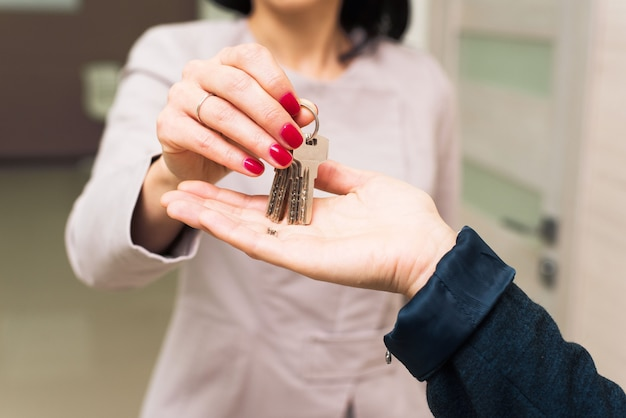 The woman passes the keys to the house or office in the hands of another person. the concept of the sale of real estate, housing, office rental