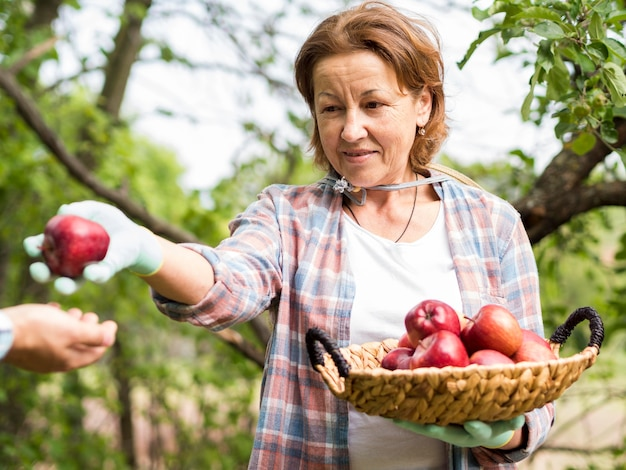 Woman passing an apple to a man