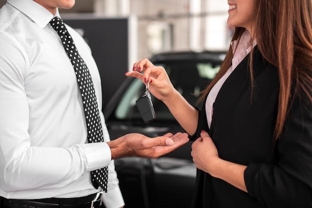 Woman passing car keys to a man
