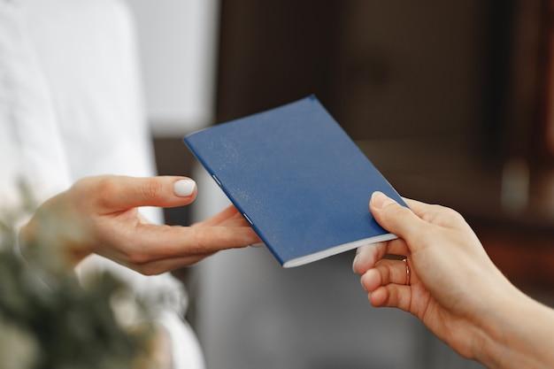 호텔 접수 원에게 그녀의 여권을 전달하는 여자