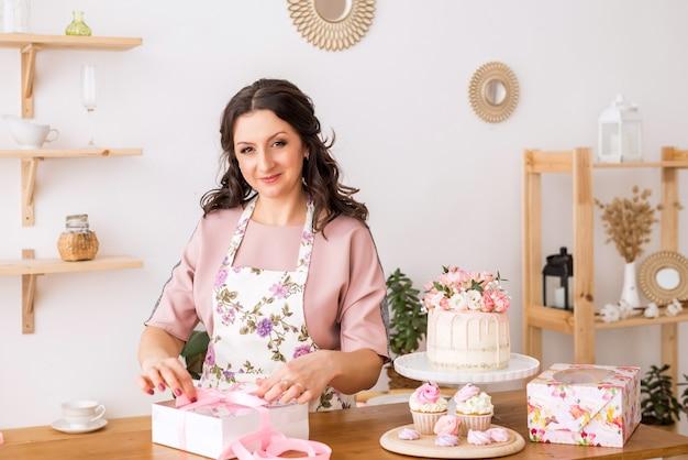 Женщина кондитер дома упаковывает домашние зефир в красивых коробках. упаковка сладостей.