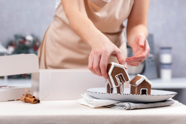 女性のパティシエがジンジャーブレッドハウスを作ります。クリスマスのお菓子を焼く。