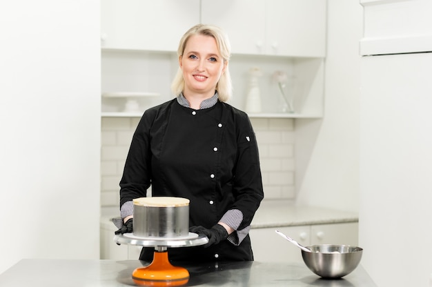 女性のパティシエがキッチンでケーキと自分を用意します。