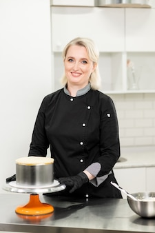 Woman pastry chef prepares a cake and herself in the kitchen.