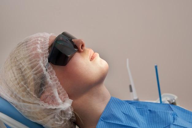 Женщина-пациент у стоматолога улыбается и ждет проверки
