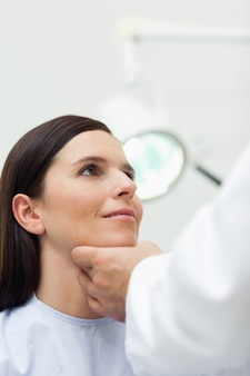 Woman patient being auscultated by a doctor