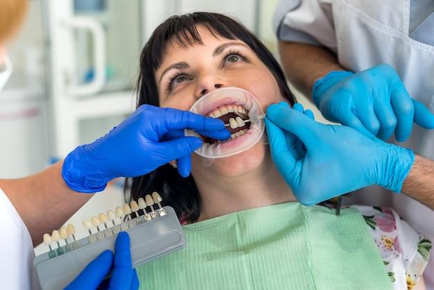 サンプラーと歯を比較する歯科医の椅子の女性患者