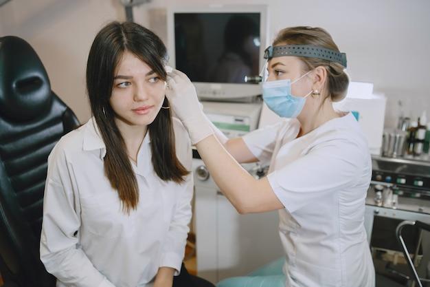 Пациент женщина в медицинском кабинете. врач в медицинской маске. лор проверяет уши женщины.