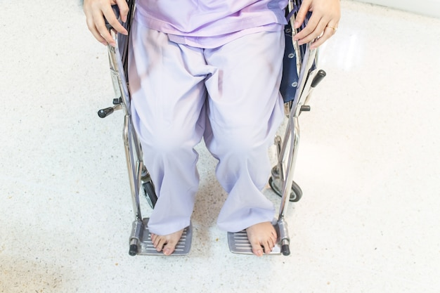 病院の廊下に座っている車椅子の女性患者