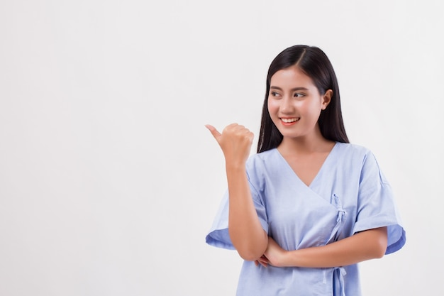 Woman patient pointing thumb up gesture away, health insurance concept