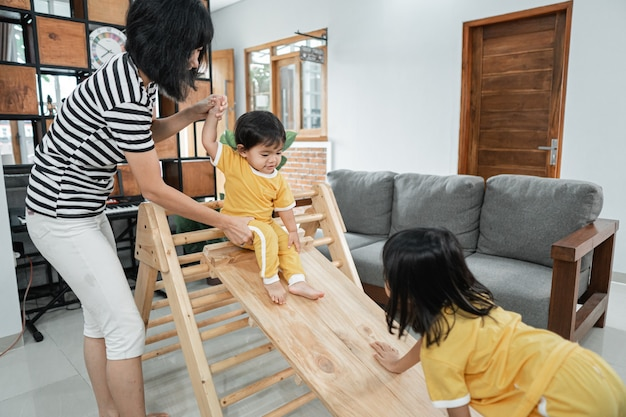 A woman patiently holding a baby while standing sliding on a pikler triangle toy at home