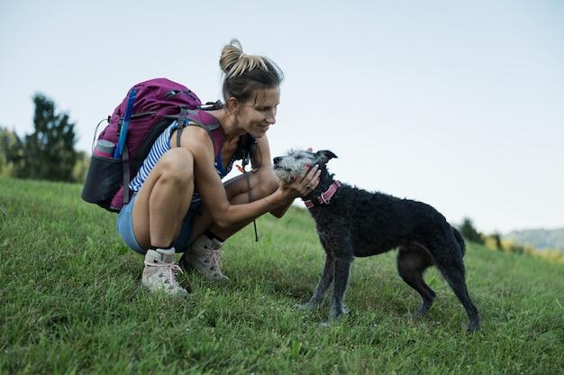 ハイキングに彼女の犬をなでる女性