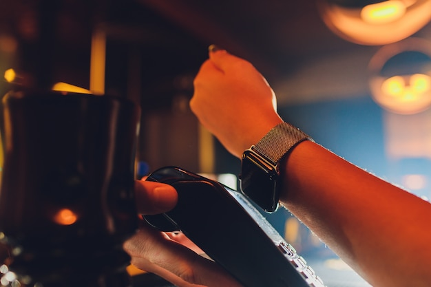 Woman pay by smart watch with nfc technology.