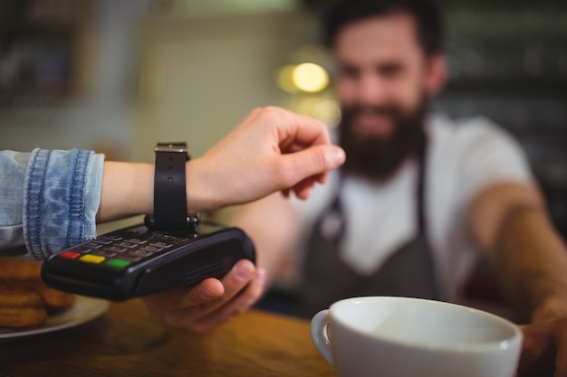 Woman paying bill through smartwatch using nfc technology