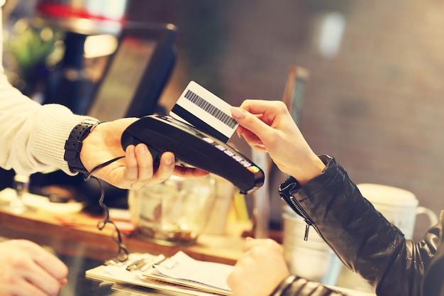 레스토랑에서 신용 카드로 지불하는 여자
