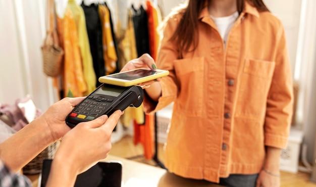 Donna che paga per i vestiti in negozio
