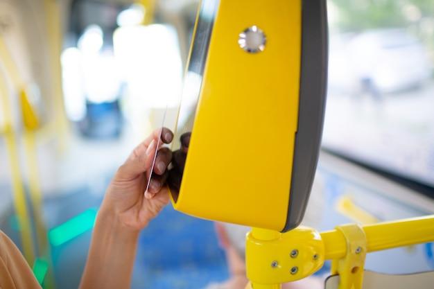 Женщина бесконтактно платит картой за автобус общественного транспорта