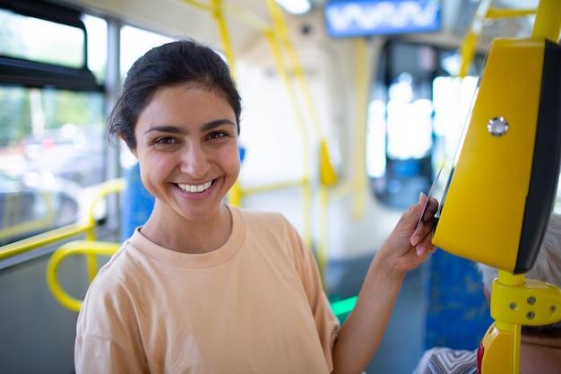 路面電車の公共交通機関にスマートフォンで無接触で支払う女性