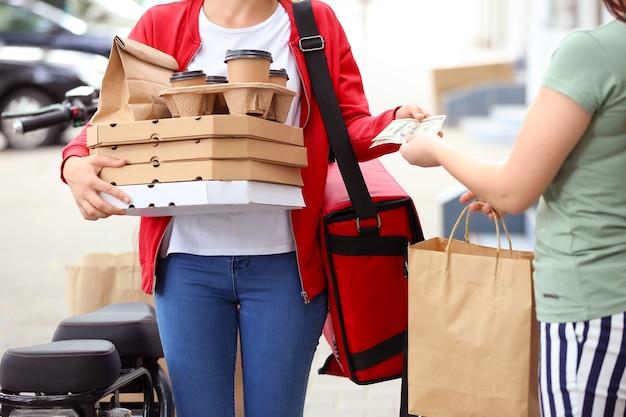 야외에서 음식 배달에 대 한 택배를 지불하는 여자