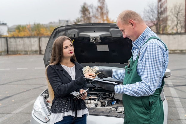 Woman paying dollars to mechanic for car diagnostic