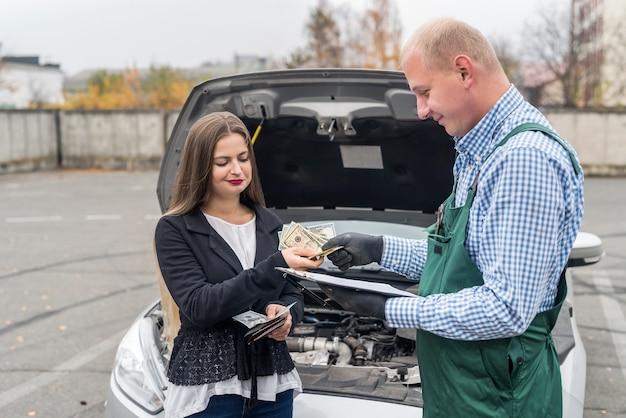 Женщина платит доллары механику за диагностику автомобиля