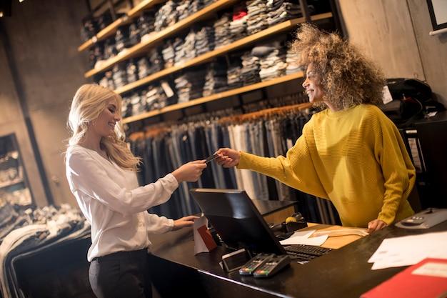 Женщина платит женскому продавцу с помощью кредитной карты в магазине одежды