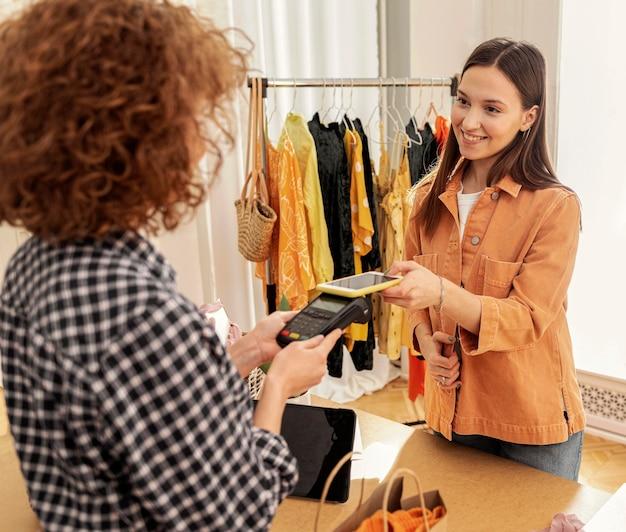 店で洋服の代金を払っている女性