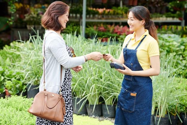 Женщина платит за комнатные растения
