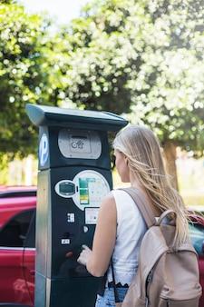 都市の貨幣機で駐車料金を支払っている女性