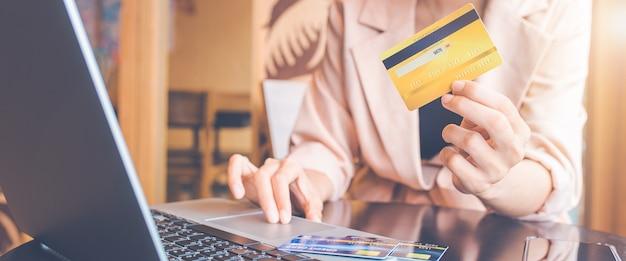 신용 카드로 온라인 청구서를 지불하는 여성입니다. 그녀는 노트북 컴퓨터를 사용하여 온라인으로 검색합니다. 웹 배너용입니다.