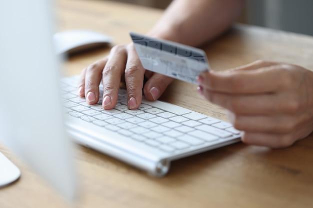 プラスチッククレジットカードのオンラインショッピングの概念でオンラインで支払う女性