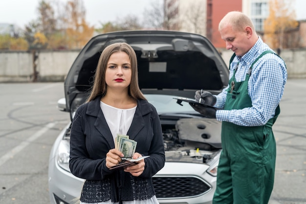 車の診断のために整備士に支払う女性