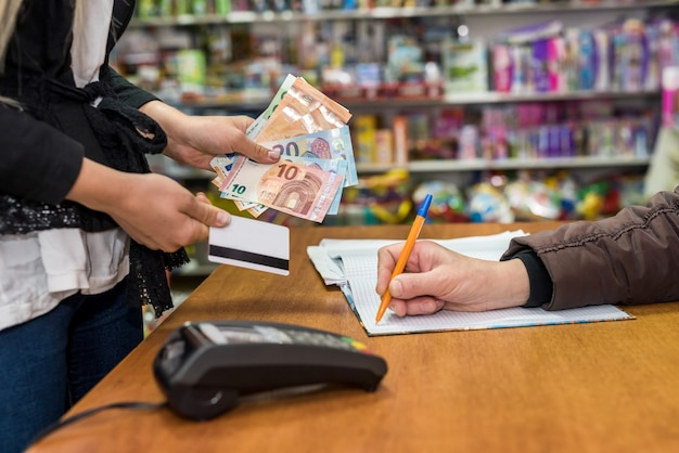 Woman paying in toy shop, seller writing in sales journal