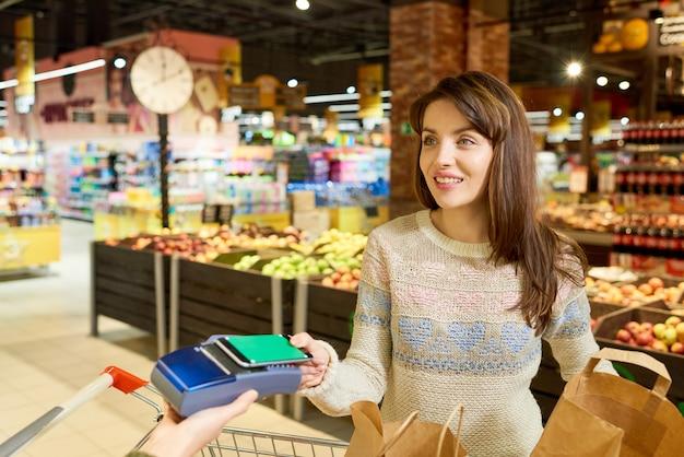 Женщина расплачивается через смартфон в продуктовом магазине