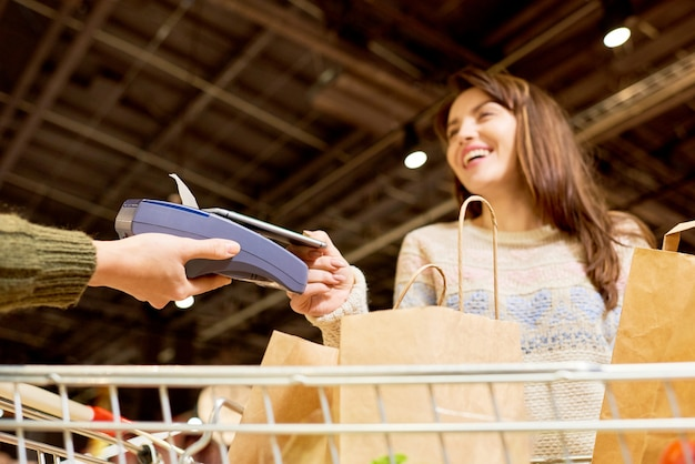 Женщина расплачивается через смартфон в супермаркете