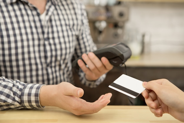 Woman paying with a credit card at the cafe