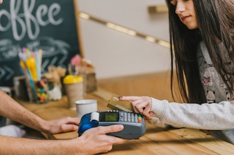 Woman paying with credit card in cafe