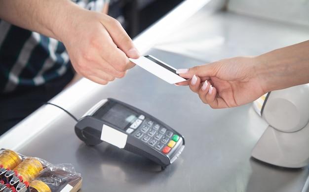 Женщина платит кредитной картой в супермаркете.