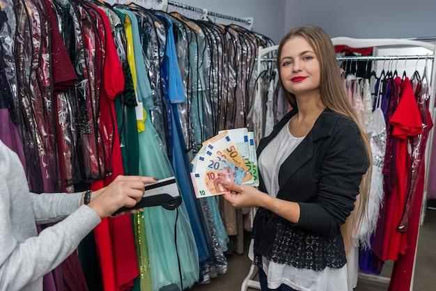 상점에서 유로 지폐로 지불하는 여자 프리미엄 사진