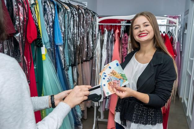 Женщина расплачивается банкнотами евро в магазине