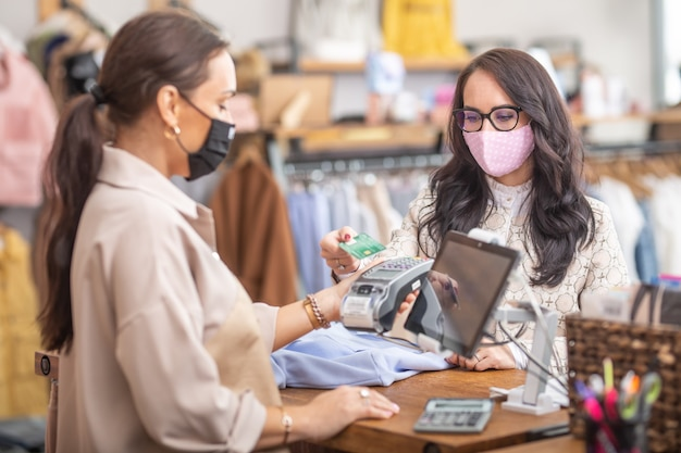 Woman pays for clothes contactless in the fashion store to the shop assistant who is holding a payment terminal, both wearing face masks.